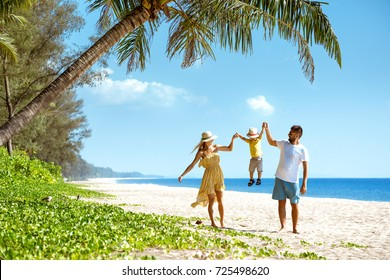 Happy family walking and having fun at sea beach. Travel or tourism concept