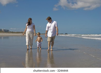 Happy family walking on a beach. Shore and blue sky in the background.
