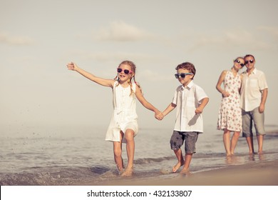 Happy family walking on the beach at the day time. Concept of friendly family.