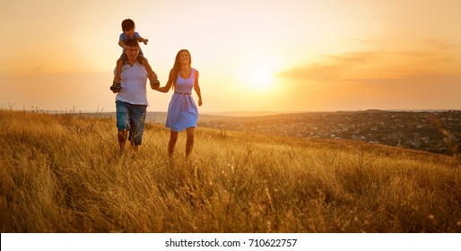 Happy family walking on field in nature at sunset