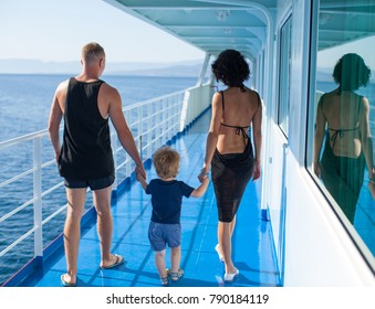 Happy family walking outdoor. Parents hold child on hands and rejoice. They are happy together. Smile each other. Luxury boat. Fashion photo. Vacation, travel, torusim, lifestyle. Summer time. Love.