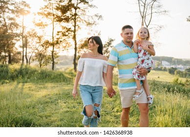 Happy family walking in the park. Mom, dad and daughter walk outdoors, parents holding the baby girl's hands. Childhood, parenthood, family bonds, marriage concept