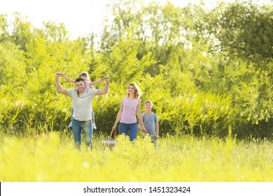 Happy family walking in park on summer day