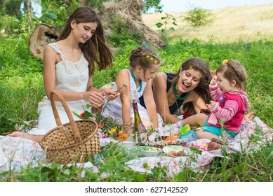 Happy family walking at the park on a sunny day. Cute family picnicking in the park. Two mothers and two daughters in a park on a picnic. Girls with their children have fun together