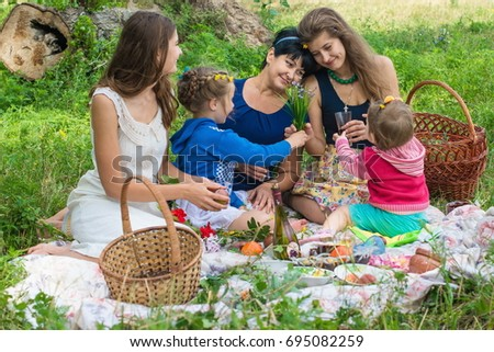 Happy family walking at the park on a sunny day. Cute family picnicking in the park.  Girls with their children have fun together. Summer picnic family.  Cute family