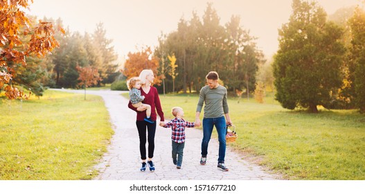 Happy family are walking through park having fun together.