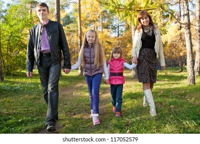 Happy family walking together in autumnal park