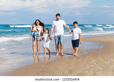 Happy family walking together on the beach
