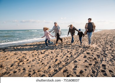 happy family walking together on seashore in autumn
