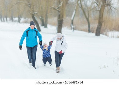 Happy family walking in the winter park