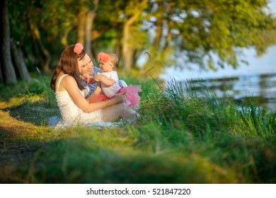 happy family walks in the park, sit on the bank of the lake and admire a decline