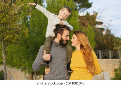 A happy family walks through the autumn park