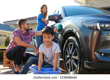 Happy family washing car at backyard on sunny day