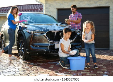 Happy family washing car at backyard on sunny day