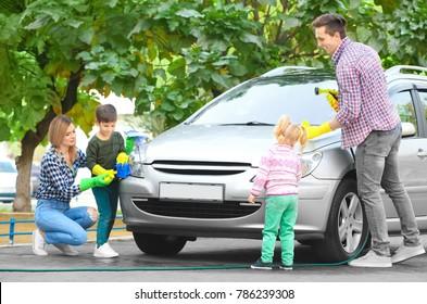 Happy family washing car outdoors