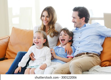 happy family watches movie while sitting on the couch