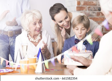 Happy family watching birthday boy blowing out candles on a cake
