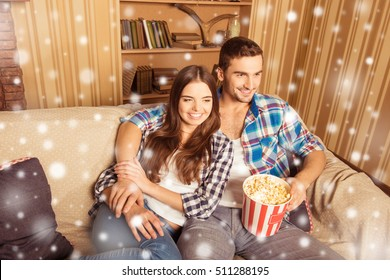 Happy family watching film with popcorn on christmas