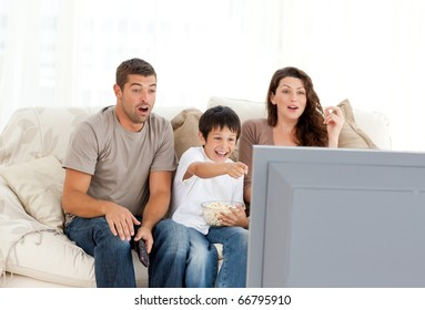 Happy family watching a movie on television together on the sofa at home