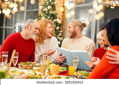 Happy family watching photo album during holiday vegetarian dinner together. Family gathering, Christmas, New year and winter holidays celebration at home with family concept