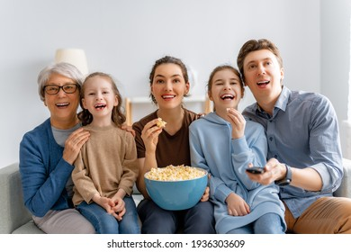 Happy family watching projector, TV, movies with popcorn  at home. Granny, mother, father and daughters spending time together.