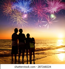 happy family watching the sunset and firework on the beach