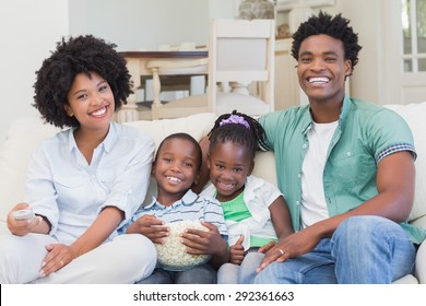 Happy family watching television eating popcorn at home in the living room
