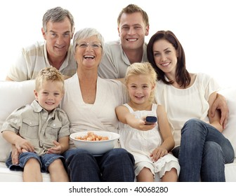 Happy family watching television and eating chips at home
