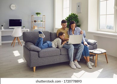 Happy family watching together video online in a laptop while sitting comfortably at home.