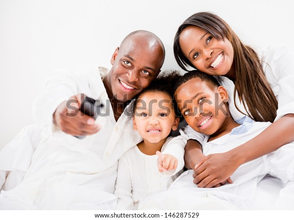 Happy family watching tv in bed - isolated over white