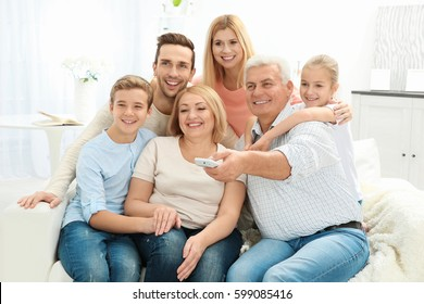 Happy family watching TV in living room