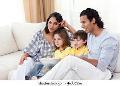 Happy family watching TV on sofa in the living room