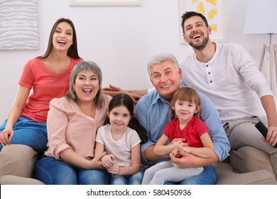 Happy family watching TV on sofa at home