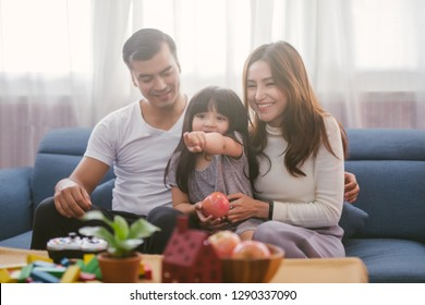 happy family watching tv together on sofa