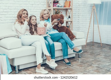 Happy Family Watching Video with Toy Bear at Home. Mother with Daughter. Smiling Women. Sitting on Sofa. Happy Family. Sitting at Home. Waching TV. Remote Control in Hand. Bucket of Popcorn.