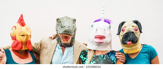 Happy family wearing different carnival masks - Crazy people having fun wearing on chicken, carlino, t-rex and unicorn mask - Concept of bizarre, humor and masquerade holidays lifestyle party