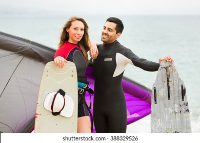 Happy family in the wetsuits with the surf boards