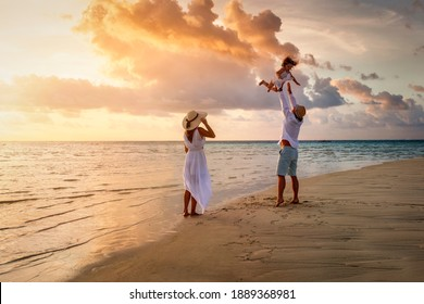 A happy family in white summer clothing is having fun on a tropical beach during sunset time