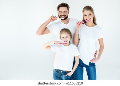 Happy family in white t-shirts cleaning teeth with toothbrushes  isolated on white
