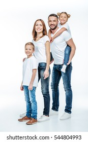 Happy family in white t-shirts and jeans standing together and looking at camera isolated on white