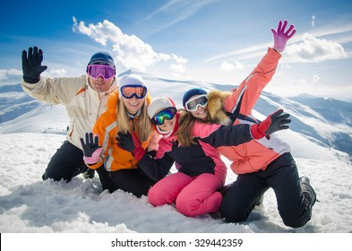 happy family in winter clothes lie on the snow at ski resort