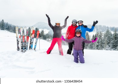 Happy family in winter clothing at the ski resort - skiing, winter, snow, fun - mom and daughters enjoying winter vacations