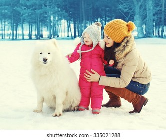Happy family in winter day, mother and child walking with white Samoyed dog in park