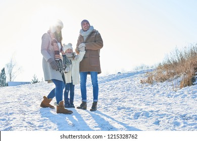 Happy family in winter holiday trip with child playing with snow