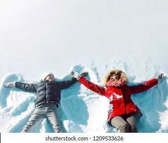 Happy family in winter! mother with son child lying on snow having fun, making snow angels, in positive, blank copy space background