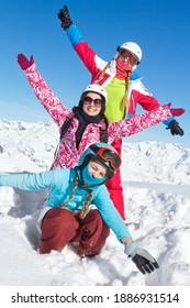 Joyeuses vacances d'hiver en famille. Trois Filles avec des vêtements très colorés posant dans la neige fraîche et le ciel bleu, et levant les mains