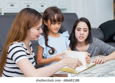 Happy family woman and kid reading book at home, happy family concept, 3 person