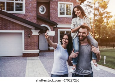 Happy family. Women is taking photo on a smart phone. Modern new house is on the background.