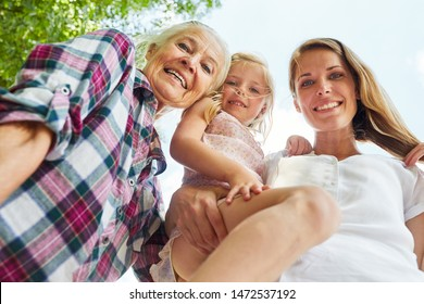 Happy family with women in three generations as extended family in summer