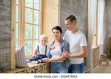 Happy family in wooden scandinavian loft interior. Family day. Little Boy with parents weared in casual denim.